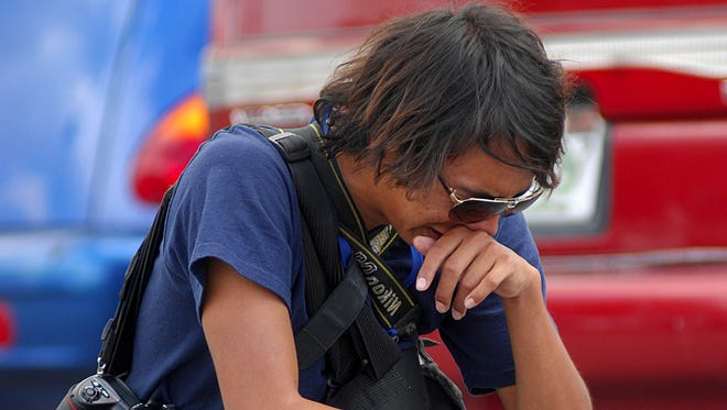 El Diario de Juarez photojournalist Christian Torres, a colleague of a slain journalist, reacts at the scene of the crime in 2010.