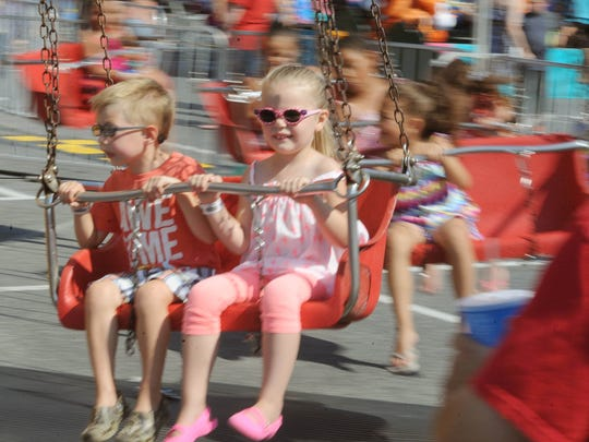 Luke Wolf of Centerville, Md., and his friend Bella Hamton, of Queen Anne, Md., both 4, whirl on one of the children's rides at the Delaware State Fair Saturday.