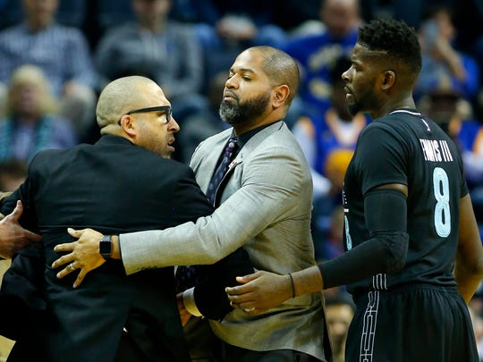 Memphis Grizzlies head coach David Fizdale (left) is restrained by assistant coach J.B. Bickerstaff (center) and Memphis Grizzlies forward James Ennis (right) at FedExForum in Memphis, on Friday, Feb. 10, 2017. Fizdale was ejected from the game.