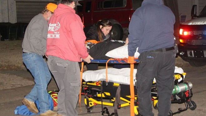 Pratt County Paramedics get assistance from bystanders to place a pedestrian on a gurney after she was struck by a vehicle Sunday night on West Blaine. The incident is under investigation by the Pratt Police Department.