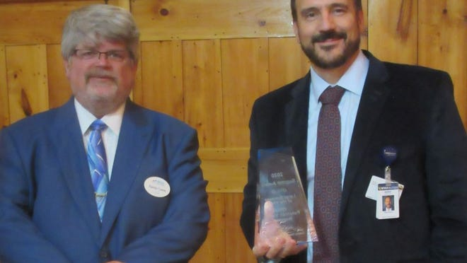 WVU Potomac Valley Hospital CEO Mark Boucot (right) accepts the Mineral County Chamber of Commerce Large Business of the Year Award from Chamber president Randy Crane during this week's Summit Awards.  Tribune photo by Ronda Wertman