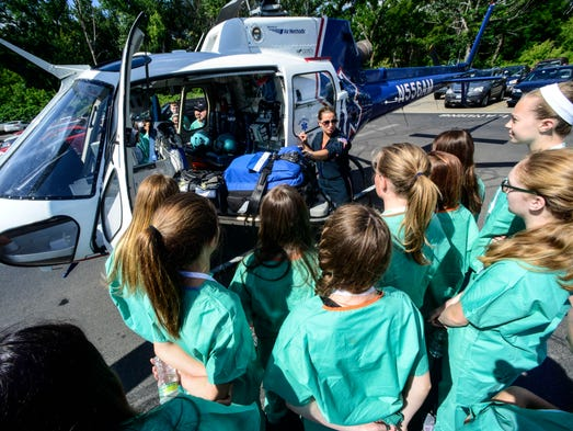 Melissa Gore, a nurse with Life Net of New York, talks to a group of student participating in Lourdes' MASH Camp on Thursday about their job in the medical field.