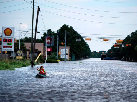 A woman paddles down a flooded road while shuttling deliveries for her neighbors during the aftermath of Hurricane Harvey on August 30, 2017 in Houston, Texas.