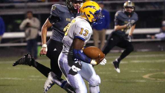 Carmel quarterback Isaac James runs down the field during the Greyhounds' 28-6 sectional win at Noblesville on Friday, Oct. 24, 2014.