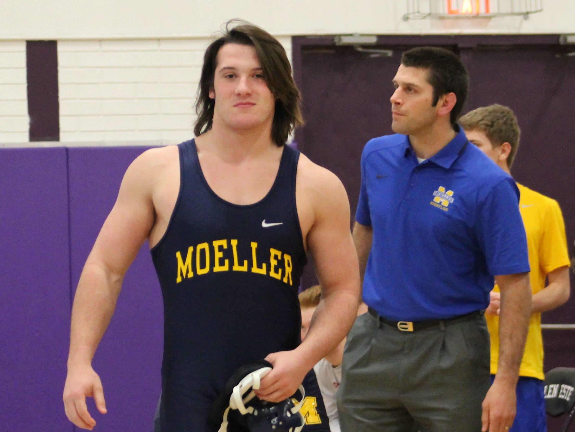 Moeller junior Jack Meyer smiles after victory with his coach James Yonushonis behind him.