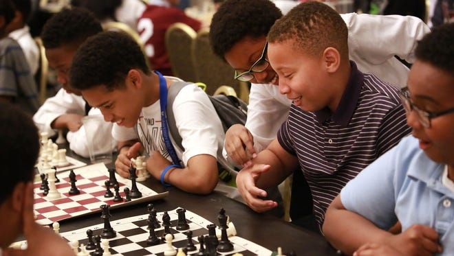 Kameron Wilson, 11, of Farmington Hills, in back, and others in the Detroit City Chess Club joke May 1 while practicing for a competition.