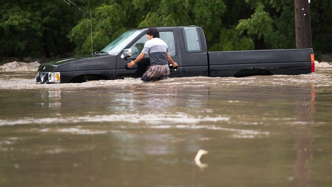 A man tries to get back into the vehicle to have it pulled out after it got stuck in high water in South Kansas City, Mo., on Thursday, July 27, 2017.  The same system is bringing heavy rain and the chance of flooding to the Mid-Atlantic on Friday and Saturday.