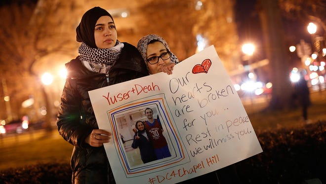 Kheira Benkreira, left, and Hasnia Bekkadja, right, attend a vigil held by the Council on American-Islamic Relations on Thursday in Dupont Circle in Washington, D.C. The vigil was held to honor three young Muslim students, Deah Shaddy Barakat, Yusor Mohammad Abu-Salha, and Razan Mohammad Abu-Salha, who were recently shot to death in Chapel Hill, North Carolina.