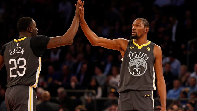 Golden State Warriors forward Kevin Durant (35) high fives Warriors forward Draymond Green (23) against the New York Knicks during the second half at Madison Square Garden.