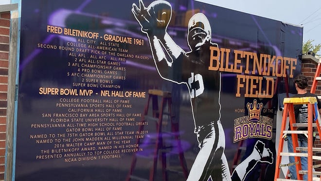 The new main sign honoring NFL great and Erie native Fred Biletnikoff was installed Wednesday at Biletnikoff Field, behind Erie High School and along Peach Street. At right is Joe Pepicello with Leader Graphics, which installed the sign.