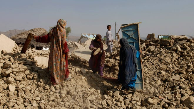 Pakistani women search their belongings through rubble of a house, which was destroyed in Tuesday's earthquake, in the remote district of Awaran in Baluchistan province, Pakistan.