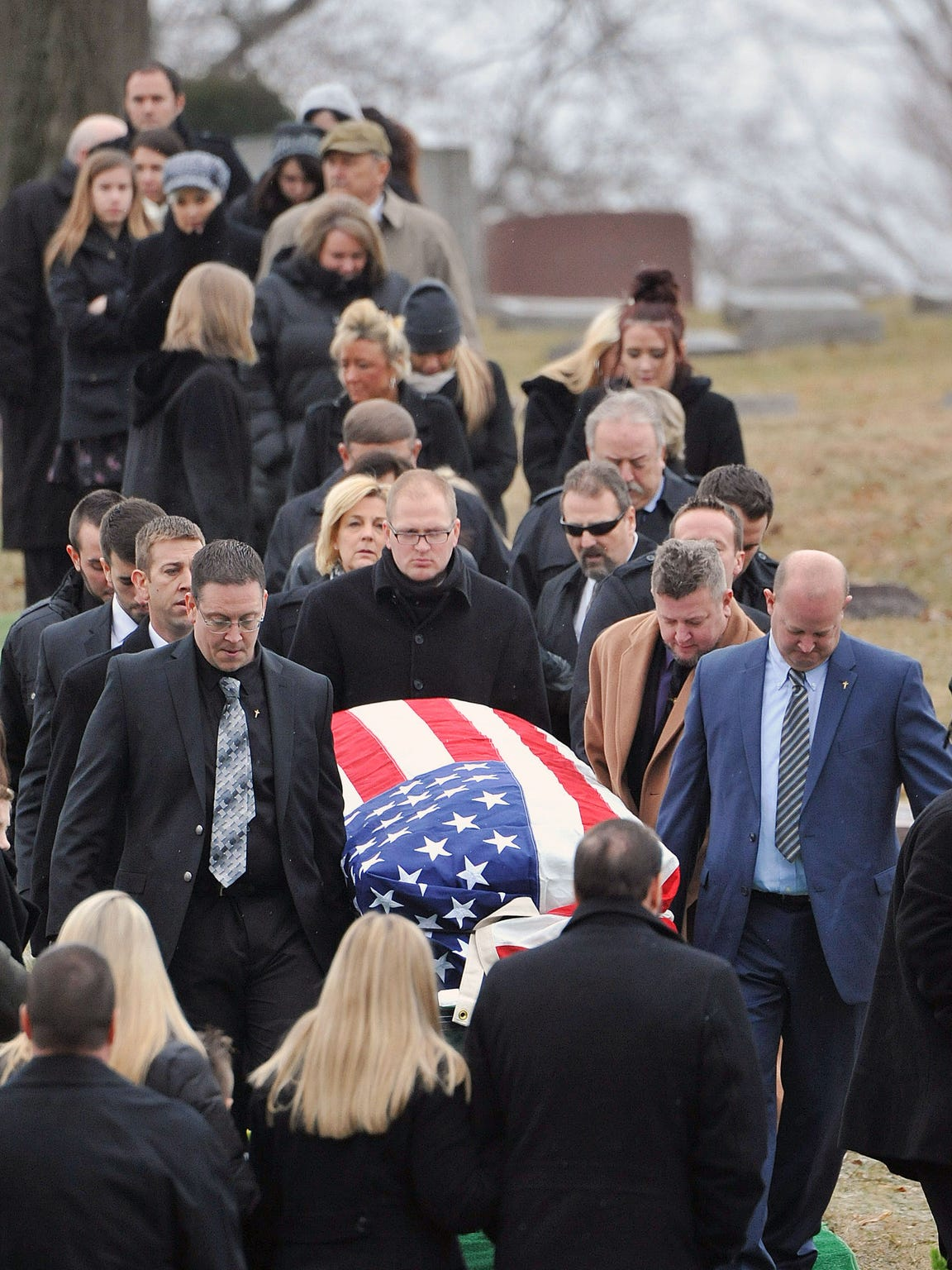 Pallbearers carry John Wendling during his funeral