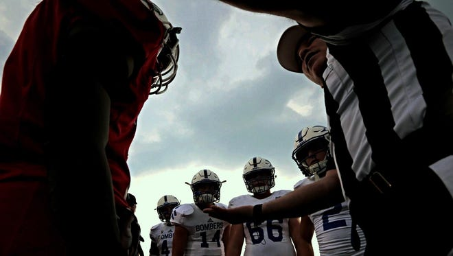 Colerain and St. Xavier players meet for the coin toss before Friday's game, which was ultimately rescheduled to Saturday.