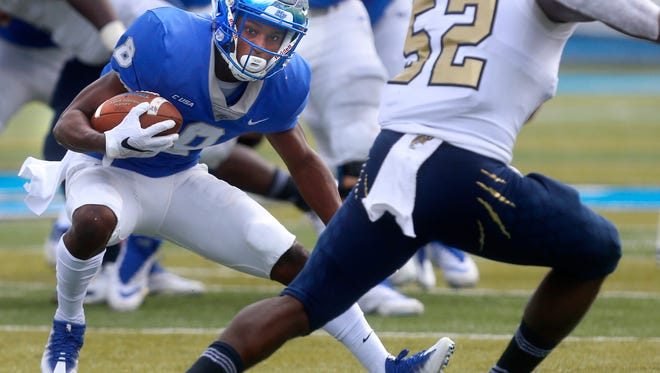 MTSU's Ty Lee (8) runs the ball as FIU's Treyvon Williams (52) moves in for the tackle during a game last season.