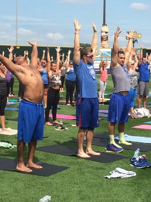 Iowa Cub players Adron Chambers, John Andreoli, Anthony Giansanti participate in a yoga session at Principal Park Saturday.