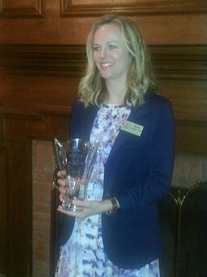 Darby Kerrigan Scott holding the 2016 Thomas M. Ervin, Jr. Distinguished Young Lawyer Award.