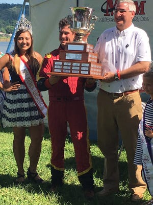 Andrew Tate (center) is handed the Governor's Cup Trophy by Indiana Gov. Eric Holcomb (right) after winning the Madison Regatta final on Sunday. July 2, 2017