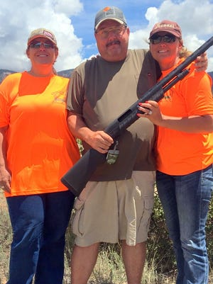Wade Westerfeld, with a score of 94 out of 100 targets, won a Remington 887 shotgun at the Aim High shooting event. He's flanked by  Rhonda Vincent and Coda Omness.