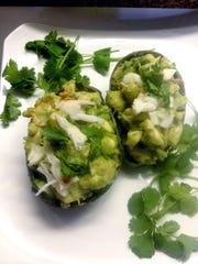 Lobster salad is piled into avocado shells.