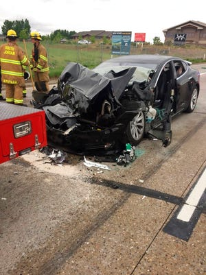 In this Friday, May 11, 2018, photo released by the South Jordan Police Department shows a traffic collision involving a Tesla Model S sedan with a Fire Department mechanic truck stopped at a red light in South Jordan, Utah.