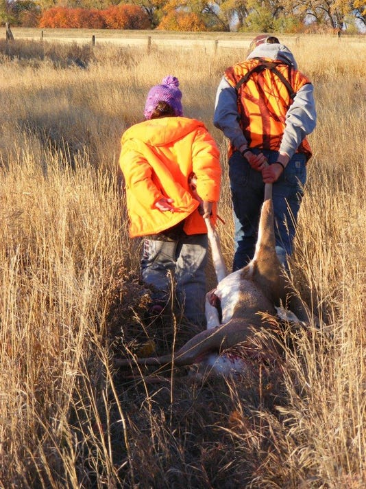 -adult and child dragging a deer.jpg_20131029.jpg