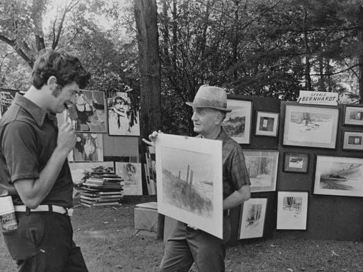 Ron Esterline (left) of the Indian Trader Co., looks over a painting by Gerald Bernhardt on display at the Penrod Arts Fair at the Indianapolis Museum of Art in 1974.