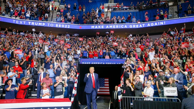 President Donald Trump walks toward the stage while supporters cheer during a campaign rally Saturday night at the BOK Center in Tulsa, Okla.