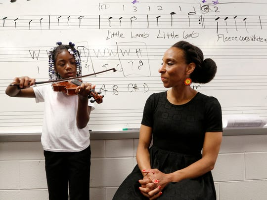 (L to R) Namiyah Coburn, 8, who is a third grader in Sean Patton's band class at Duke Ellington at William J. Beckham Detroit Public School in Detroit,demonstrates playing Ode to Joy on her one-fourth size violin as her violin teacher Leslie DeShazor, a guest instructor who plays for the Detroit Symphony Orchestra looks on.