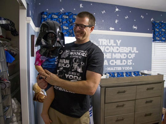 Huge Star Wars fan Andrew Stewart holds his son, Elliott, 2, in their Chandler home on May 10, 2018.