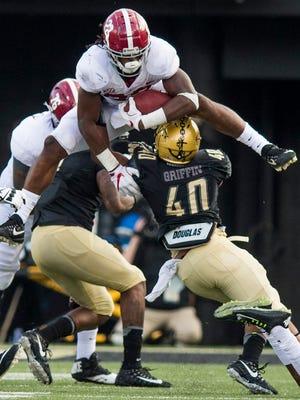 Alabama running back Najee Harris (22) leaps over Vanderbilt linebacker Jordan Griffin (40) at Vanderbilt Stadium in Nashville, Tenn. on Saturday September 23, 2017. (Mickey Welsh / Montgomery Advertiser)