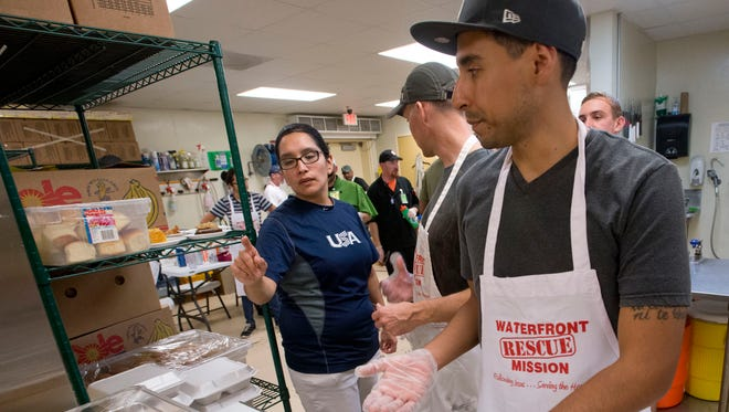 Joy Committee member, Sara Rios, left, gives last minute instructions to Brady Noltie, right, and other volunteers preparing to serve the Christmas Eve dinner at the Waterfront Rescue Mission.