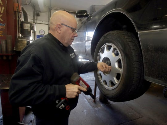 Mario Aloia, owner Post Road Service and Tire Center in White Plains, removes a tire from a car so he can check the brakes, Feb. 16, 2017.