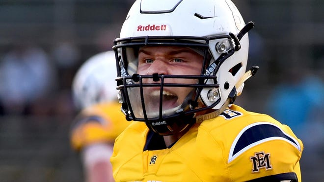 Erie Mason senior quarterback yells out after throwing a touchdown pass in his home opener on September 25. Due to the coronavirus pandemic a plastic shield was installed on their helmets.