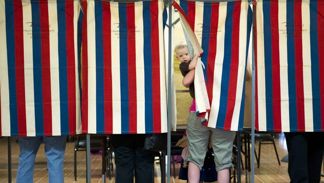 Landon Peterson peeks out of the voting booth while his mother, Meghan, votes on March 20, 2012, in Metamora, Ill.