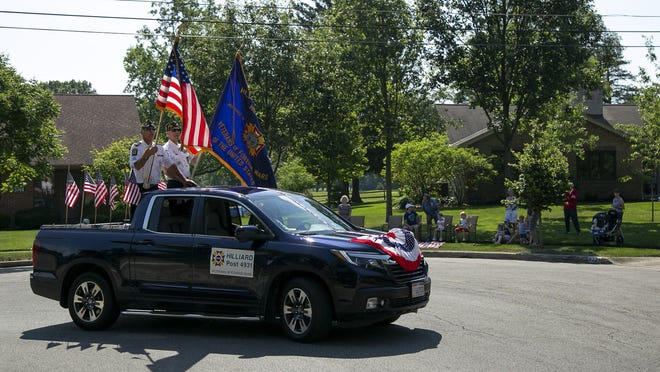 Two veterans hold flags on the back of a pickup turning from Lyon Drive onto Grace Lane during the Upper Arlington Civic Association's Fourth of July parade Saturday.