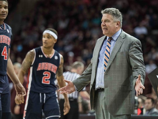 Auburn head coach Bruce Pearl, right, reacts after