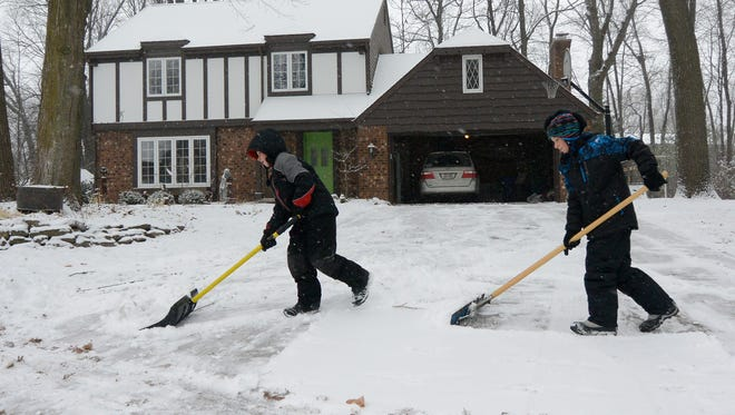 Landon Drews, 9, left, and his brother Forrest Drews, 10, shovel their driveway Wednesday in Appleton. The two say they are saving up the snow to build a fort.