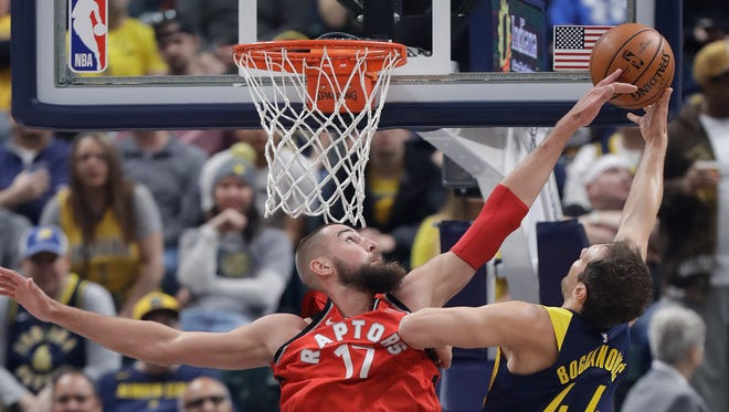 Indiana Pacers' Bojan Bogdanovic has his shot blocked by Toronto Raptors' Jonas Valanciunas during the first half of an NBA basketball game Thursday, March 15, 2018, in Indianapolis.