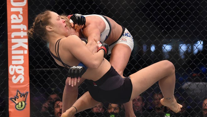 Ronda Rousey (red gloves) competes against Holly Holm (blue gloves) during UFC 193.