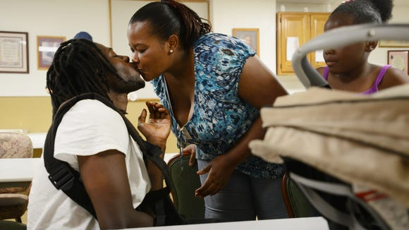 Tiana Jackson gives Lavar Bailey, her partner of seven years, a kiss hello in the morning.   6/18/14