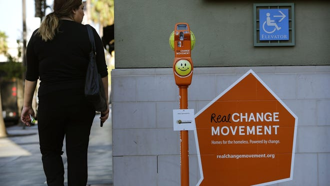 A passerby glances at a parking-meter like machine used for collecting money for  homeless people last month in Pasadena, Calif. Pasadena is installing these machines around the city to collect money that will go into a fund where organizations serving homeless people can apply for it.