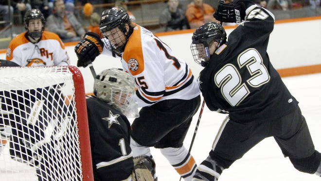 RIT senior co-captain Ben Lynch, center, tries to tip a puck past Army goaltender Rob Tadazak, left, as defenseman Luke Jenkins closes in during the Tigers' 6-0 win on Friday.