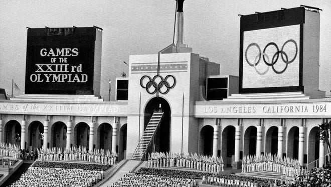 In this July 28, 1984 file photo, the Olympic flame is flanked by a scoreboard signifying the formal opening of the XXIII Olympiad after it was lit by Rafer Johnson during the opening ceremonies in the Los Angeles Memorial Coliseum. Boston, Los Angeles, San Francisco and Washington are the cities still in the running for a possible U.S. bid to host the 2024 Summer Olympics.