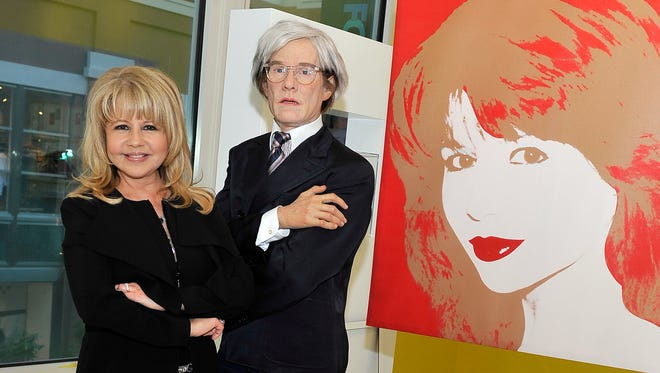 Pia Zadora poses with a waxy Warhol (and his portrait of her) at the Polaroid Museum opening at The Linq.