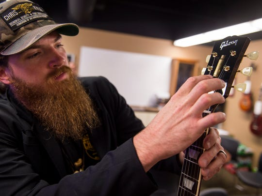 Nashville country artist Tim Montana inspects a shell