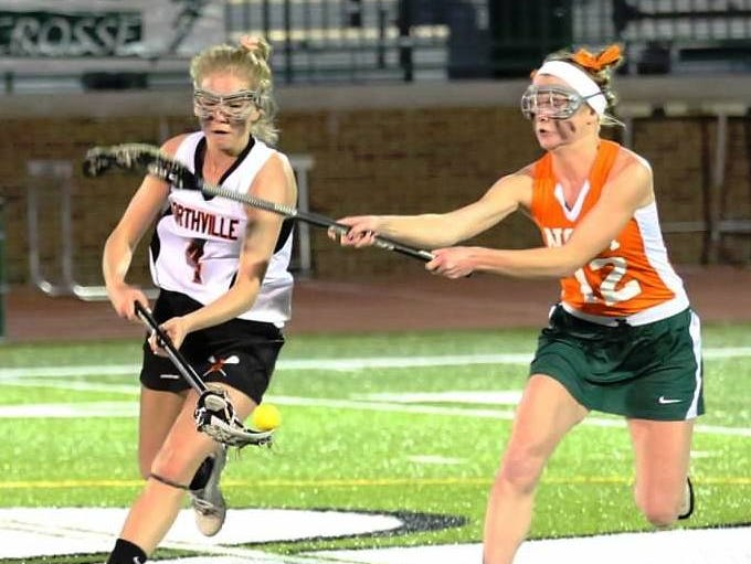 Northville's Sarah Chase (left) tries to keep the ball away from Novi's Alanna Clark.