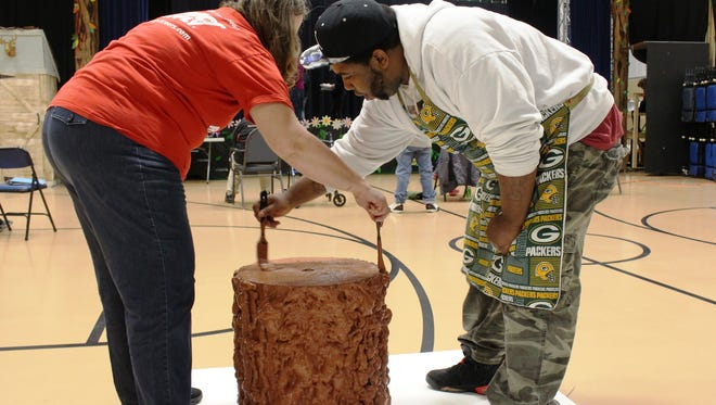 Dominique Riggins and Rene Sundling, new employees at Sargento Foods, paint a prop for an upcoming play while volunteering at RCS Empowers on Monday, March 6, in Sheboygan.