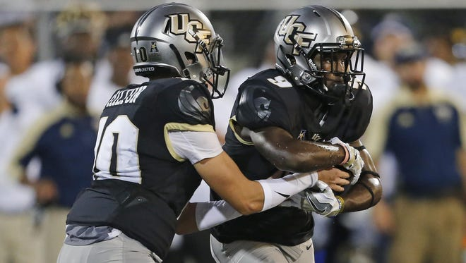 Mckenzie Milton hands off to Adrian Killins during a game earlier this season. Killins, a freshman, has 310 yards and three touchdowns this season.