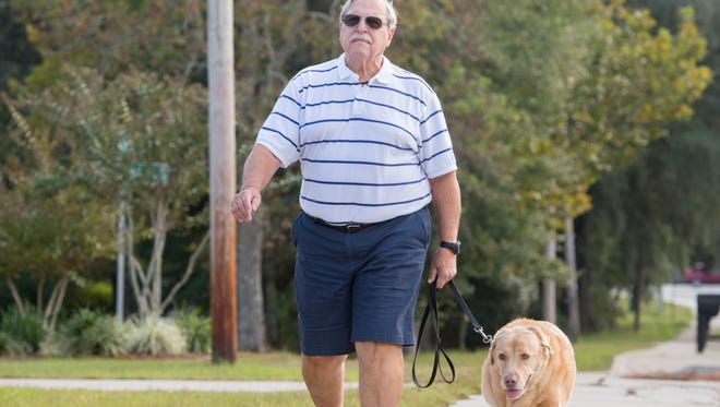 Thanks to two hip and two knee replacement surgeries performed by the Andrews Institute, Jay Botop is able to walk his dog Tristan without the use of a walker or cane outside of his home in Pensacola.  November 2, 2017.