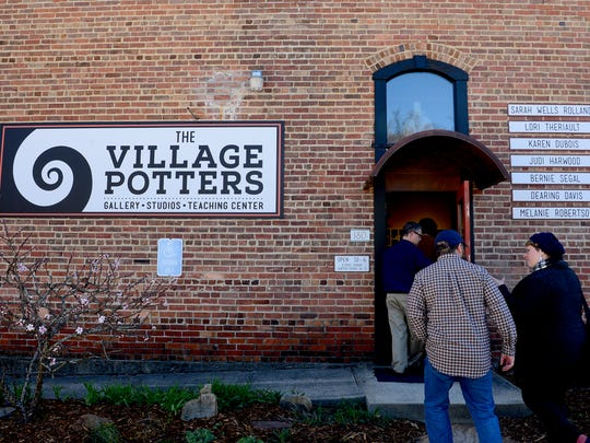 Participants of a collaboration between Asheville Art Studio Tours and Leap Frog Tours enter The Village Potters studio in the River Arts District to meet some of the potters.